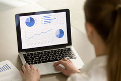 Onderneemster die aan laptop werken, die statistieken, software analyseren royalty-vrije stock afbeelding