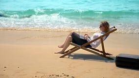 Onderneemster die aan laptop werken terwijl het zitten in een lanterfanter door het overzees op een wit zandig strand freelance o stock foto