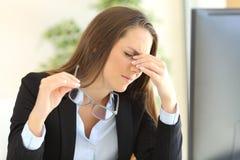 Onderneemster die aan vermoeidheid van de ogen lijden op kantoor stock fotografie