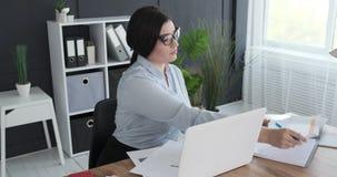 Onderneemster die administratie doen op kantoor stock videobeelden