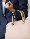 Onderneemster die beige handtas houden Stock Fotografie