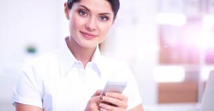 Onderneemster die bericht met smartphonezitting verzenden in het bureau Royalty-vrije Stock Afbeeldingen