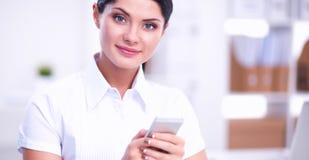 Onderneemster die bericht met smartphonezitting verzenden in het bureau Stock Fotografie