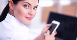 Onderneemster die bericht met smartphonezitting verzenden in het bureau Royalty-vrije Stock Afbeelding