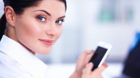 Onderneemster die bericht met smartphonezitting verzenden in het bureau Stock Afbeeldingen