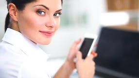 Onderneemster die bericht met smartphonezitting verzenden in het bureau Royalty-vrije Stock Fotografie