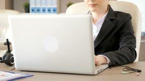 Onderneemster die bij haar bureau dan het stoppen van de audio en michrophonekoorden in laptop typen stock footage