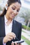 Onderneemster die bluetooth oortelefoon en PDA gebruikt Stock Foto's