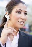 Onderneemster die bluetooth oortelefoon met behulp van stock foto