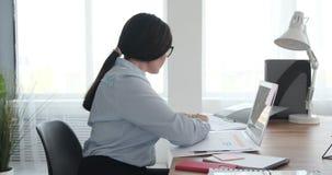 Onderneemster die documenten analyseert terwijl het schrijven op zelfklevende nota stock videobeelden