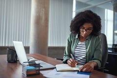 Onderneemster die in een agenda op een bureau op kantoor schrijven stock foto