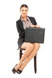 Onderneemster die een aktentas houden en op een stoel wachten royalty-vrije stock afbeeldingen