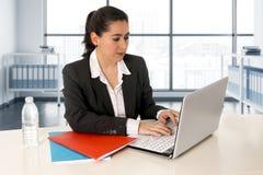 Onderneemster die een pak dragen die aan laptop computer bij moderne bureauruimte werken royalty-vrije stock fotografie