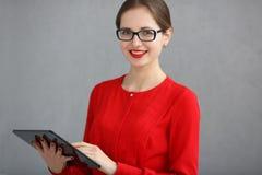 Onderneemster die in een rood overhemd en glazen een tablet in zijn handen op een grijze achtergrond houden Stock Foto's