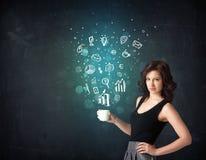 Onderneemster die een witte kop met bedrijfspictogrammen houden Royalty-vrije Stock Afbeeldingen