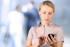 Onderneemster die en de mobiele slimme telefoon houden met behulp van Stock Foto