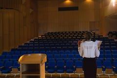 Onderneemster die en het leren manuscript terwijl status in het auditorium praktizeren royalty-vrije stock foto