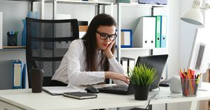 Onderneemster die en laptop in modern bureau met behulp van geeuwen stock video