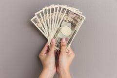 Onderneemster die geld geven en 10.000 Japans Yengeld houden op grijze muurachtergrond, Japanse Yen in hand Royalty-vrije Stock Afbeelding