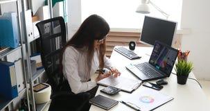 Onderneemster die glazen opstijgen en camera onderzoeken, die aan laptop in modern bureau werken stock videobeelden