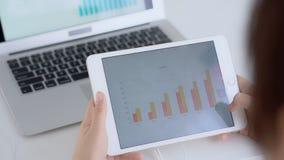 Onderneemster die grafiek en grafiekfinanciën van marketing met gegevensinformatie analyseren over tablet en laptop computer stock videobeelden