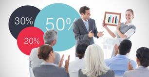 Onderneemster die grafiek tonen terwijl collega's die tegen grafiek toejuichen Stock Foto