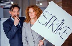 Onderneemster die grote affiche met woordstaking houden Stock Foto