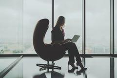 Onderneemster die haar laptop in luxebureau met behulp van royalty-vrije stock foto's