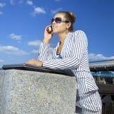 Onderneemster die haar mobiele telefoon met behulp van Stock Fotografie