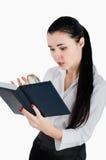 Onderneemster die het boek met vergrootglas op een wit kijken Royalty-vrije Stock Afbeeldingen