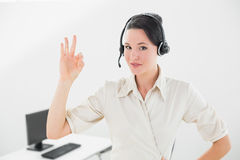 Onderneemster die hoofdtelefoon dragen terwijl het gesturing van o.k. teken in bureau Stock Afbeeldingen