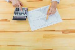 Onderneemster die investeringsgrafieken met calculator voor financiële gegevens analyseren die het tellen analyseren stock foto