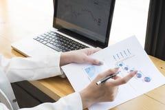 Onderneemster die investeringsgrafieken met laptop analyseren Royalty-vrije Stock Foto's