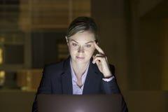 Onderneemster die laat in haar bureau aan laptop, nachtlicht werken Stock Afbeelding