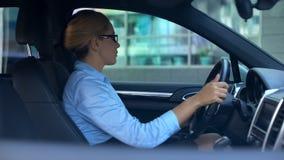 Onderneemster die langzaam auto drijven dichtbij autosalon, testaandrijving vóór aankoop stock foto