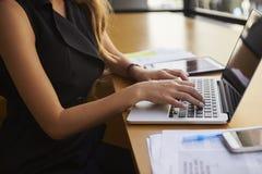 Onderneemster die laptop in bureau, medio sectie, zijaanzicht met behulp van Stock Foto's