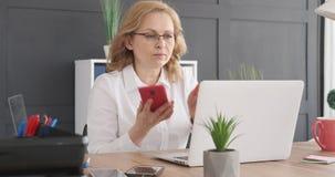 Onderneemster die laptop en mobiele telefoon met behulp van op kantoor stock video