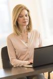 Onderneemster die laptop met behulp van bij bureau in bureau Stock Foto