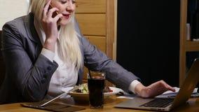 Onderneemster die lunch eten en aan laptop in de koffie werken stock video