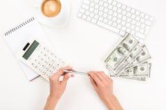 Onderneemster die met calculator en dollarbankbiljetten op het werk werken Stock Afbeeldingen