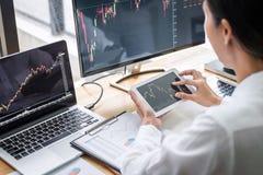 Onderneemster die met computer, laptop werken, denkend en analyserend grafiekeffectenbeurs handel met de gegevens die van de voor stock foto