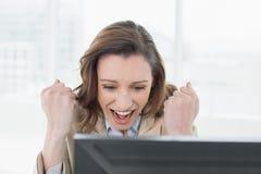 Onderneemster die met dichtgeklemde vuisten bij bureau toejuicht Stock Foto