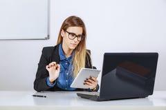 Onderneemster die met digitale tablet en laptop werken Stock Foto