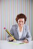 Onderneemster die met een reuzepotlood schrijven Stock Fotografie