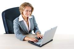 Onderneemster die met laptop in camera glimlacht Royalty-vrije Stock Foto