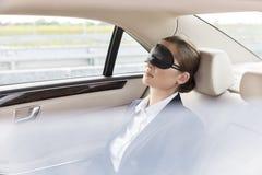 Onderneemster die met masker in auto tijdens reis dutten royalty-vrije stock afbeeldingen