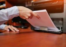 Onderneemster die met printer in het bureau werken stock afbeelding