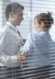 Onderneemster die met zijn collega in bureau flirten stock afbeelding