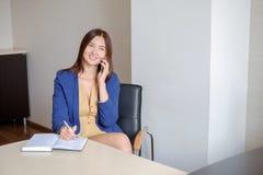 Onderneemster die mobiel telefoongesprek nemen en nota's schrijven in kalender bij bureau Stock Foto's