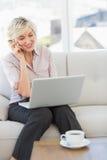 Onderneemster die mobiele telefoon en laptop thuis met behulp van Stock Foto's